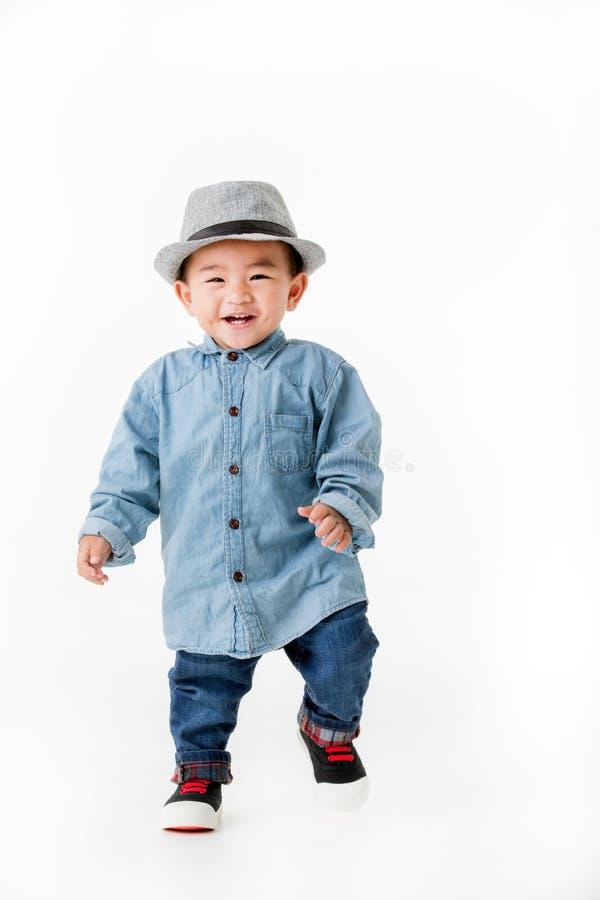 Bebê asiático do bebê de um ano no shurt das calças de brim que senta-se no jogo do assoalho foto de stock