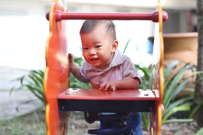 Bebê asiático no campo de jogos imagens de stock