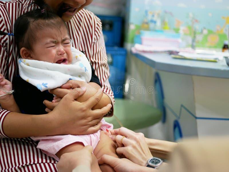 Bebê asiático pequeno, bebê de um ano, gritando na dor após as enfermeiras pediatras que dão lhe uma vacinação fotografia de stock royalty free