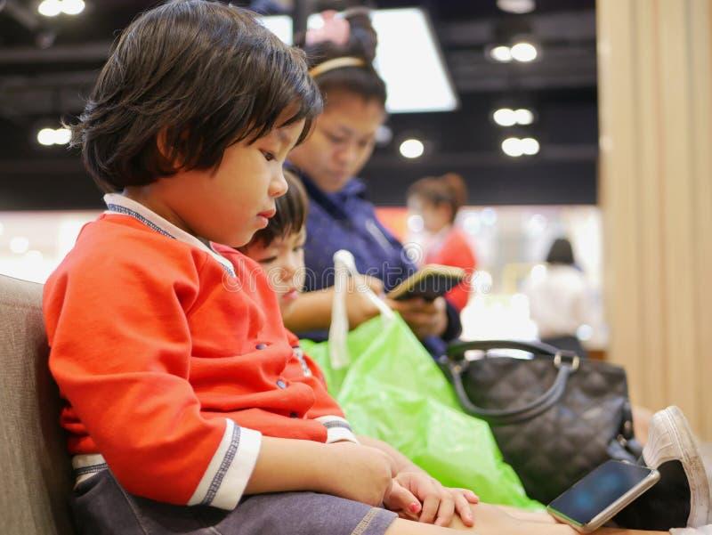 Bebê asiático pequeno, junto com sua irmã mais nova, olhando um smartphone, mesmos que sua mamã, sentando e esperando uma fila foto de stock