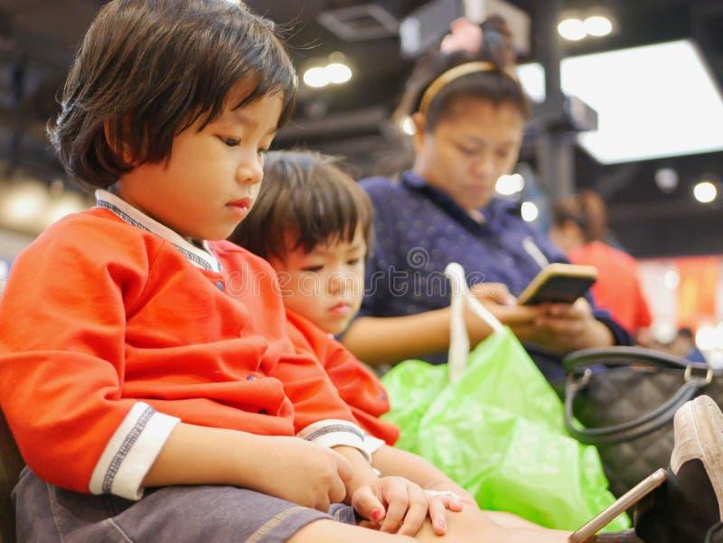 Bebê asiático pequeno, junto com sua irmã mais nova, olhando um smartphone, mesmos que sua mamã, sentando e esperando uma fila imagem de stock