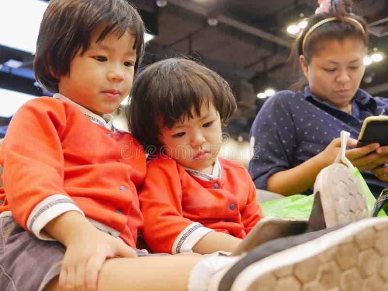 Bebê asiático pequeno, junto com sua irmã mais nova, olhando um smartphone, mesmos que sua mamã, sentando e esperando uma fila fotos de stock royalty free