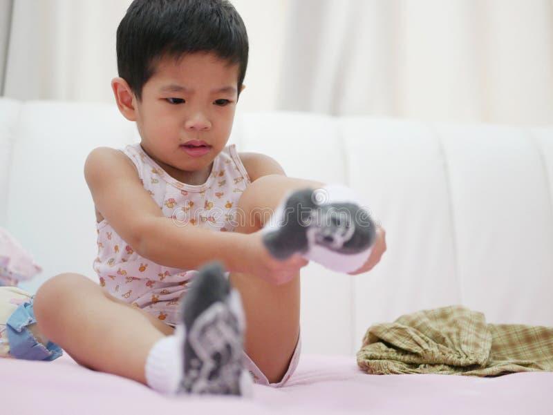 Bebê asiático pequeno que é whiny quando tentar pôr sobre peúgas fotos de stock