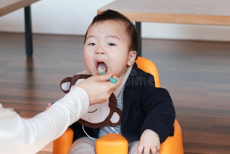 Bebê asiático que come o comida para bebê foto de stock
