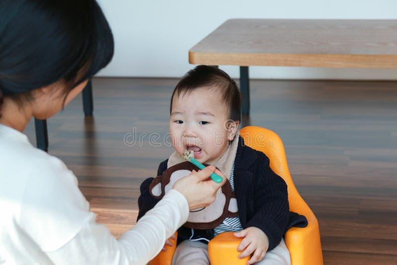 Bebê asiático que come o comida para bebê foto de stock royalty free