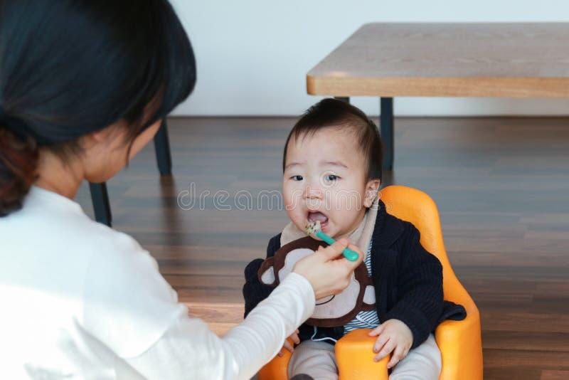 Bebê asiático que come o comida para bebê imagem de stock