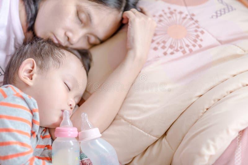 Bebê asiático que dorme no braço da mãe fotos de stock