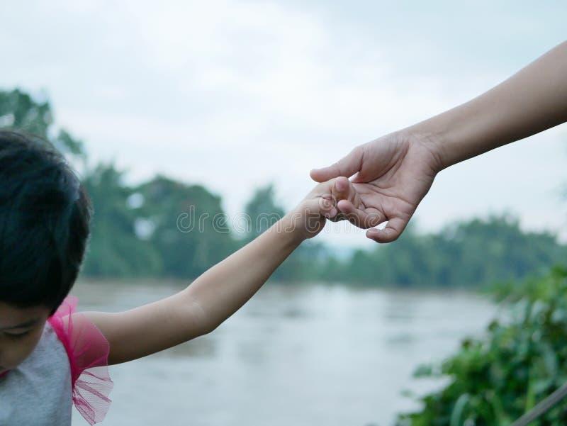 Bebê asiático que guarda seu dedo da mãe para a segurança ao tentar deprimir alguém uma terra mais baixa foto de stock royalty free