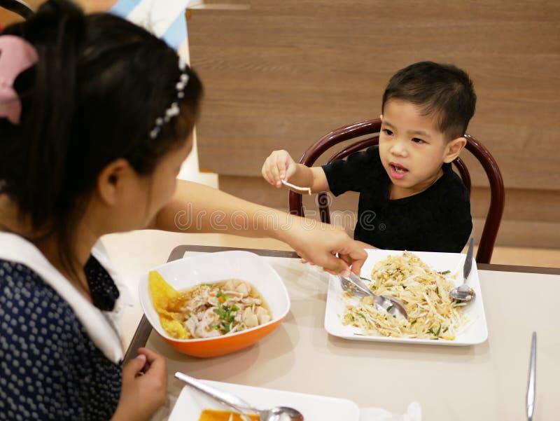 Bebê asiático que pegara um beansprout de seu alimento e que negocia com a mamã para não o comer foto de stock