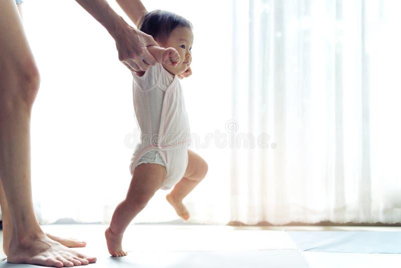 Bebê asiático que toma primeiramente etapas para andar para a frente na esteira macia fotos de stock royalty free