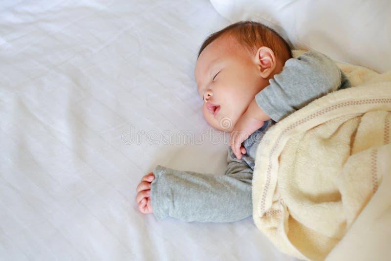 Bebê asiático recém-nascido calmo que dorme na cama com a cobertura foto de stock