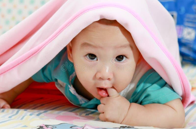 Bebê asiático sob o cobertor cor-de-rosa fotografia de stock royalty free