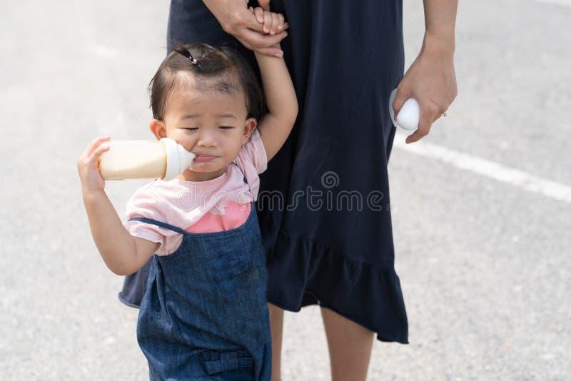 Bebê bonito asiático que come o leite na garrafa imagens de stock royalty free