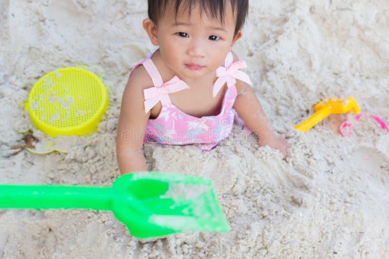 Bebê bonito asiático que joga brinquedos na praia da areia imagens de stock royalty free