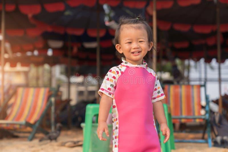Bebê bonito asiático que sorri no fundo da praia imagens de stock royalty free