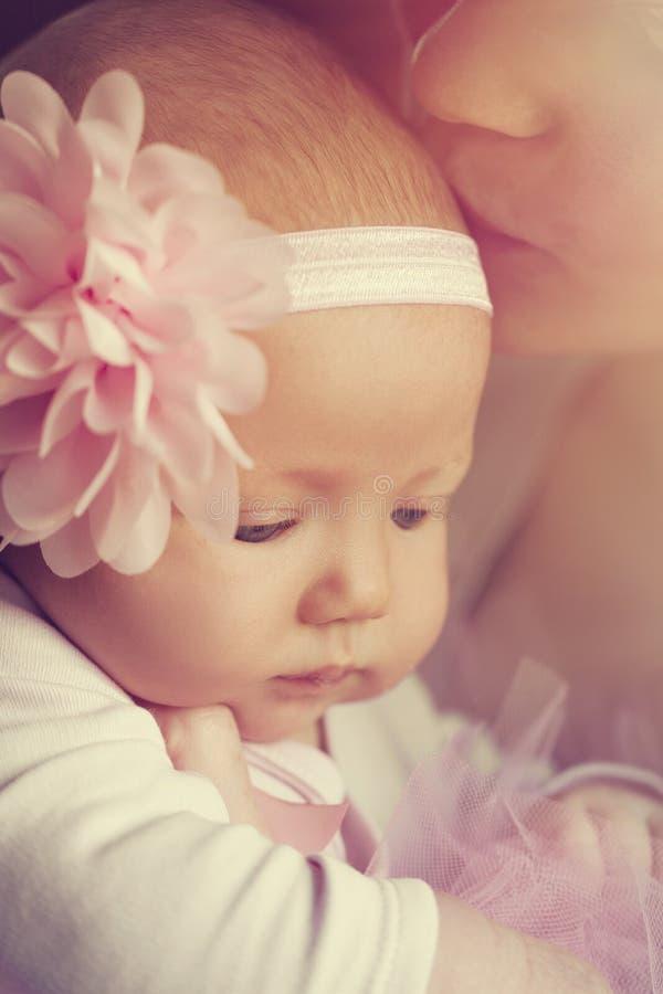 Bebê bonito bonito com a fita cor-de-rosa bonita com seu mot imagem de stock royalty free