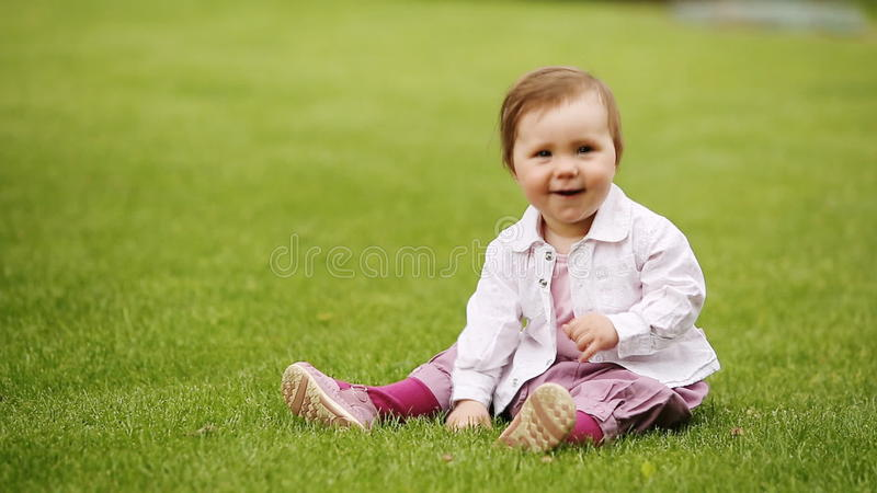 Bebê bonito bonito pequeno que senta-se na grama verde no cidade-parque video estoque