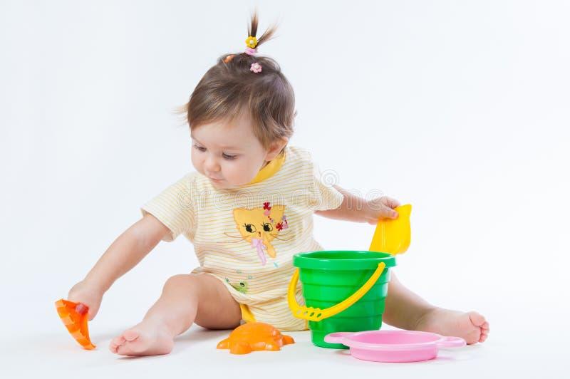 Bebê bonito com a cubeta e a pá isoladas no fundo branco imagens de stock royalty free