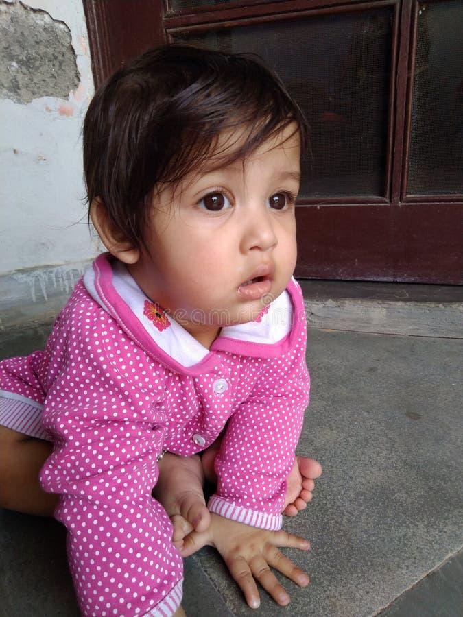 Bebê bonito com os olhos marrons no terno cor-de-rosa dos às bolinhas imagem de stock royalty free