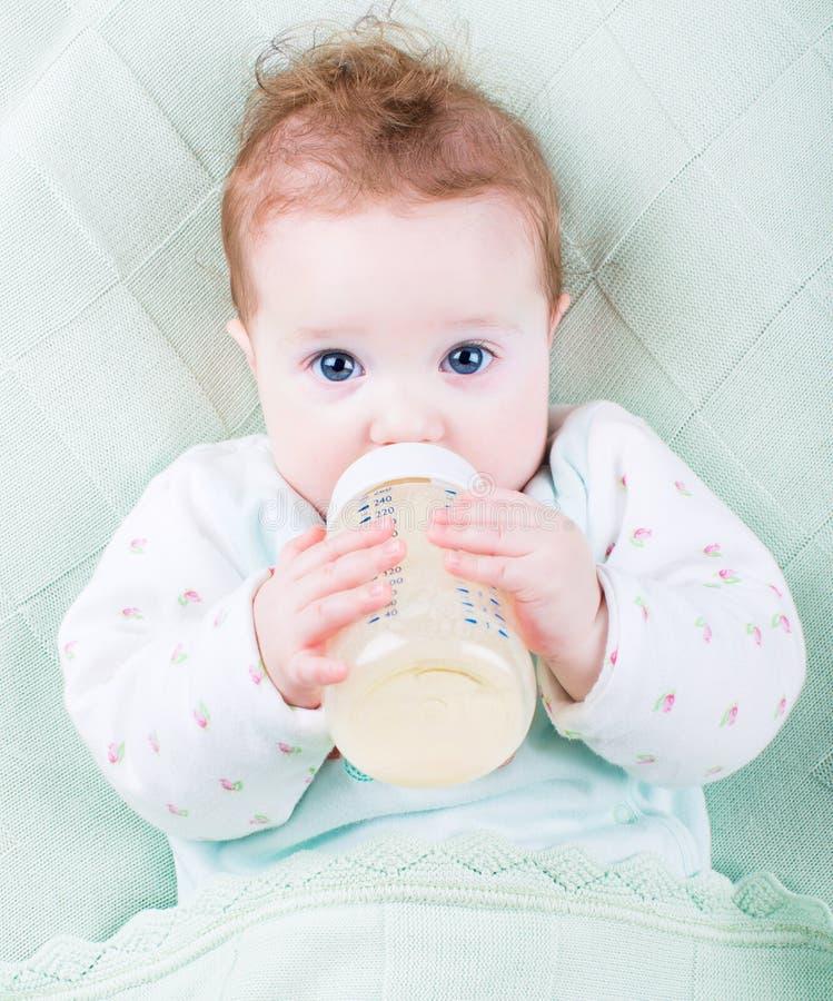 Bebê bonito com uma garrafa de leite sob uma cobertura feita malha morna fotografia de stock
