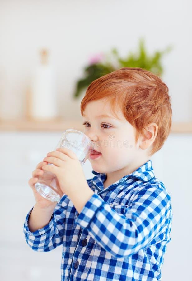 Bebê bonito da criança que bebe a água fresca do vidro cedo na manhã fotografia de stock royalty free