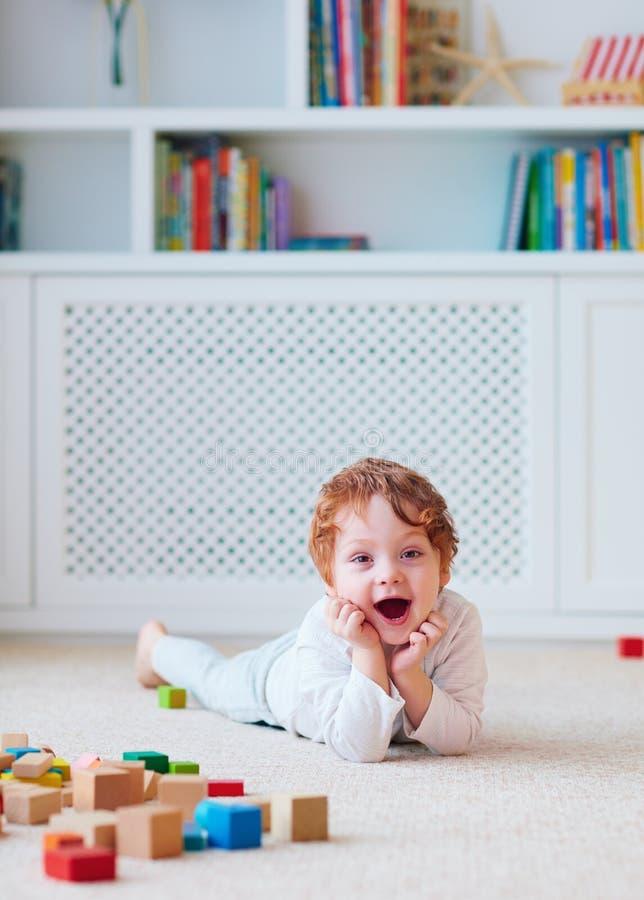 Bebê bonito da criança que joga com blocos de madeira no tapete fotos de stock royalty free