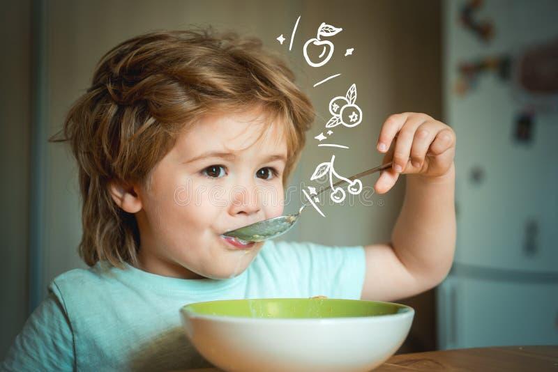 Bebê bonito de riso da criança que senta-se no cadeirão e que come no fundo borrado A criança alegre do bebê come o alimento próp fotos de stock