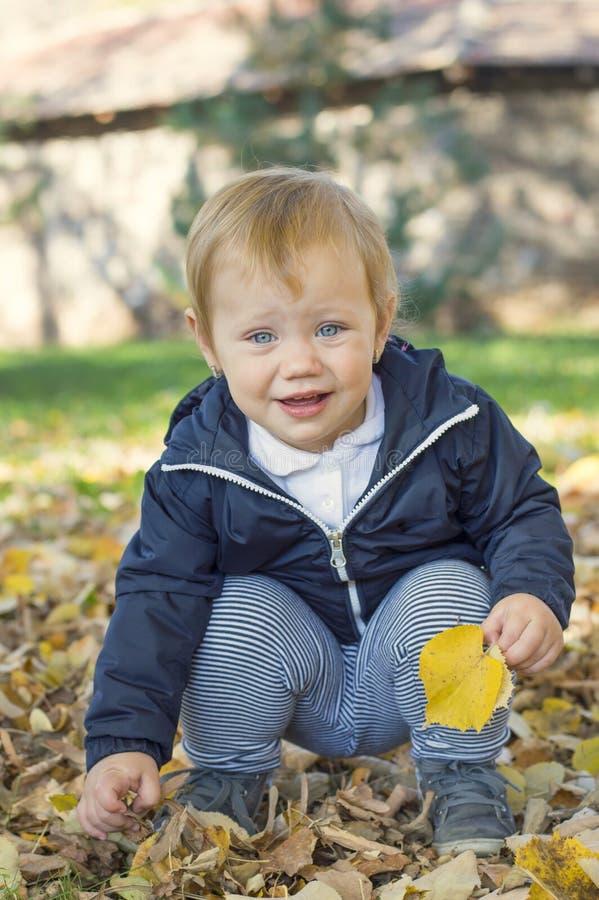 Bebê bonito do bebê de um ano que senta-se na grama em um parque foto de stock