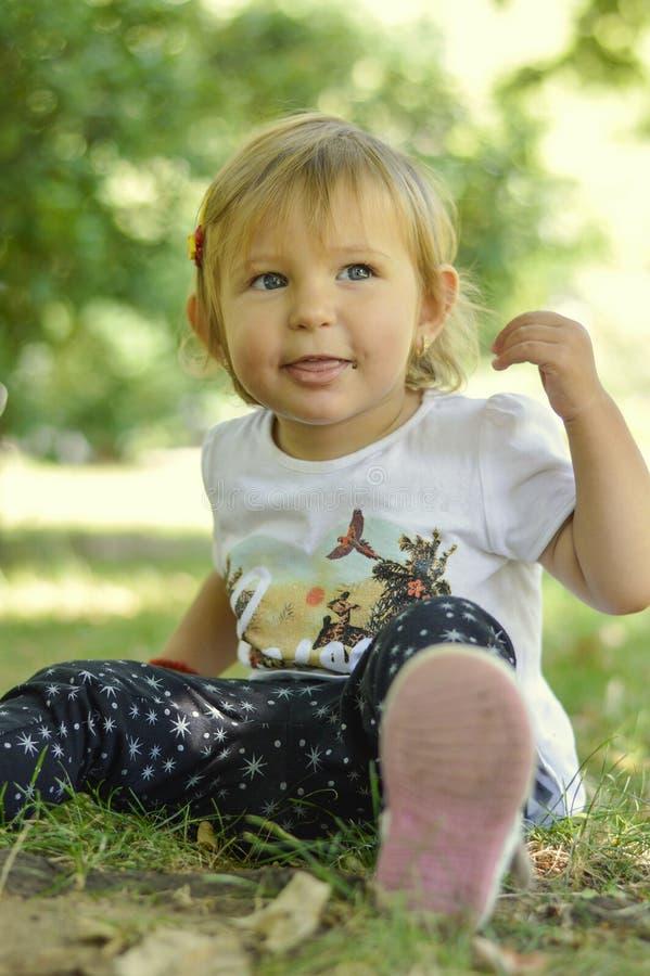 Bebê bonito do bebê de um ano que senta-se na grama no parque imagem de stock