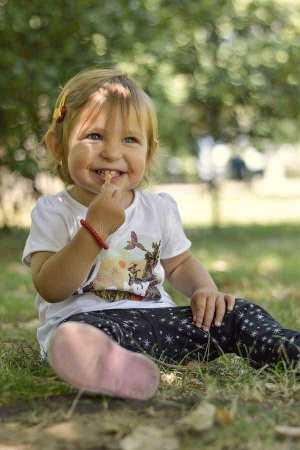 Bebê bonito do bebê de um ano que senta-se na grama no parque fotografia de stock royalty free