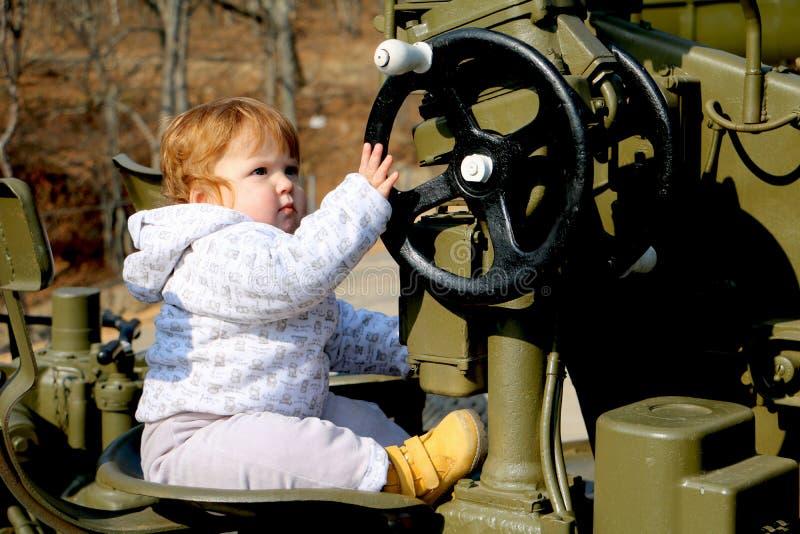 Bebê bonito do gengibre que senta-se no volante do exército militar imagens de stock royalty free