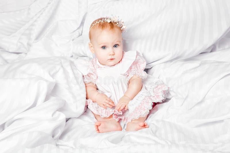 Bebê bonito e consideravelmente novo no vestido agradável sobre a cobertura branca fotografia de stock