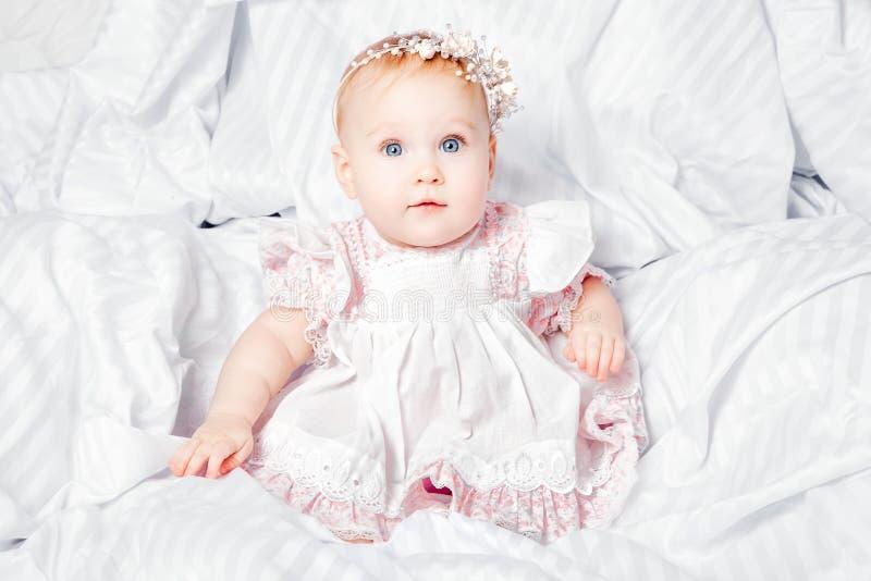 Bebê bonito e consideravelmente novo no vestido agradável sobre a cobertura branca imagem de stock royalty free