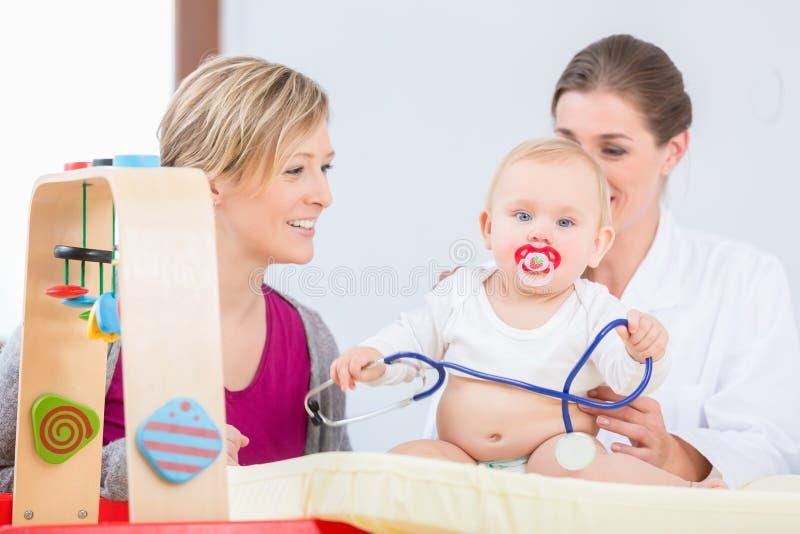 Bebê bonito e saudável que joga com o estetoscópio durante o exame fotografia de stock