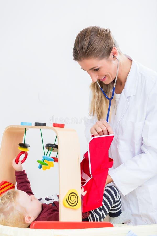 Bebê bonito e saudável que joga com o estetoscópio durante r imagens de stock