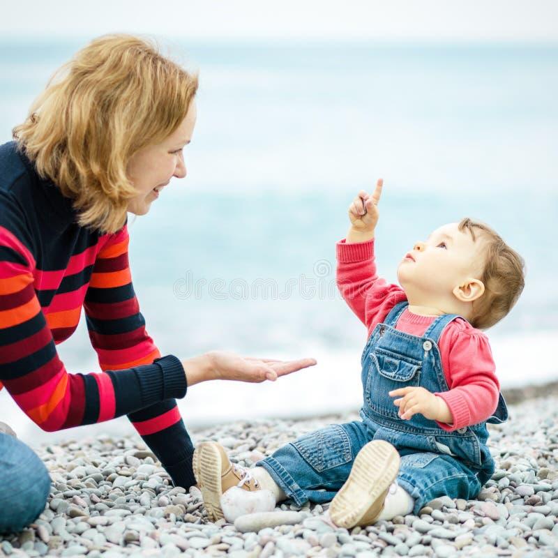 Bebê bonito e sua mãe que jogam com os seixos na praia fotos de stock royalty free
