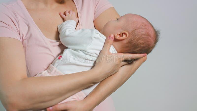 Bebê bonito em seus braços das mães imagem de stock royalty free
