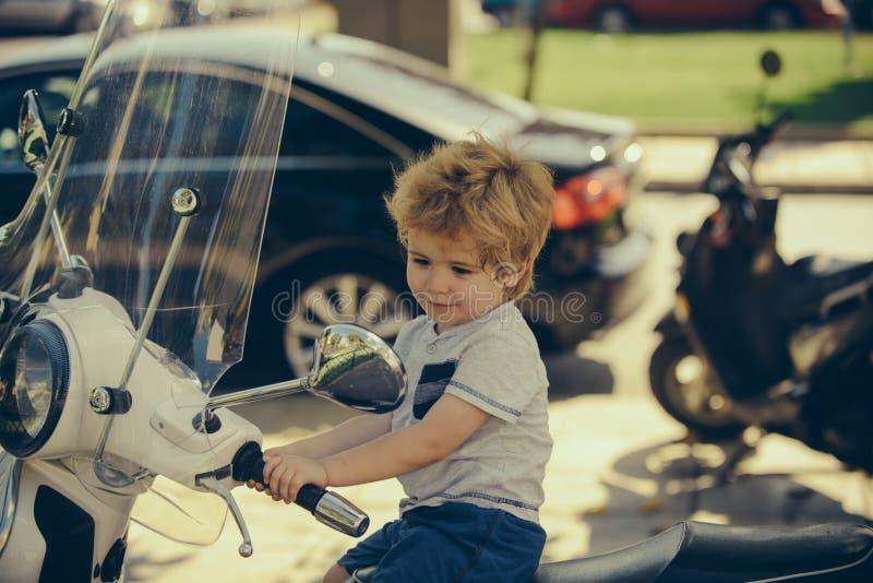 Bebê bonito em uma motocicleta Viagem do ver?o aventura Transporte para o curso Excitador pequeno Conceito grande do menino feliz foto de stock royalty free
