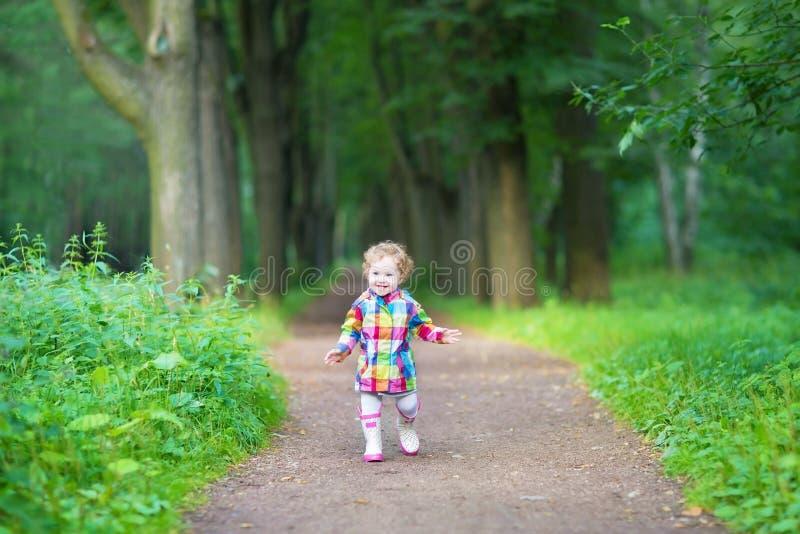 Bebê bonito nas botas de chuva de borracha que anda no parque chuvoso imagem de stock