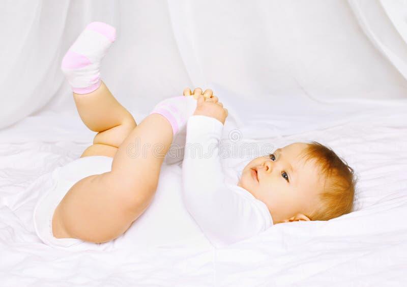 Bebê bonito nas peúgas que encontram-se na cama e que guardam os pés fotos de stock royalty free