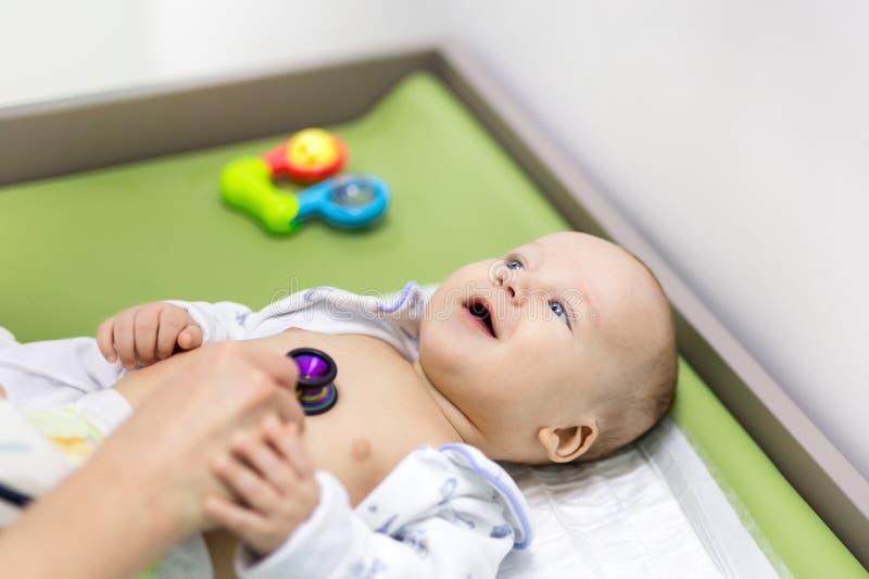 Bebê bonito no armário do ` s do doutor Pediatra que faz o exame da criança com estetoscópio Criança saudável de sorriso Crianças imagem de stock