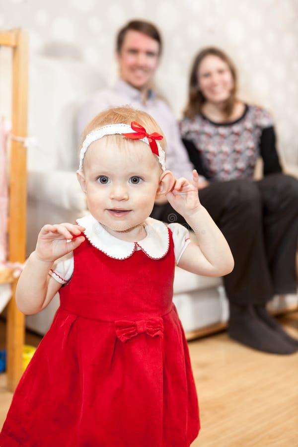 Bebê bonito no vestido vermelho e nos pais que sentam-se no fundo imagem de stock