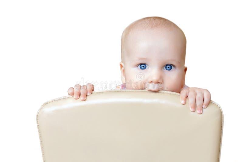 Bebê bonito pequeno que morde para trás da cadeira na cozinha Criança do divertimento que espreita para fora o chairback na sala  fotos de stock royalty free