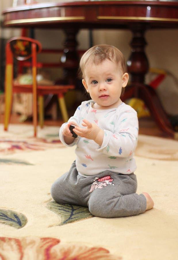 bebê bonito pequeno que senta-se em seus joelhos no children& x27; sala de s no fundo da tabela e de uma variedade de brinquedos fotografia de stock
