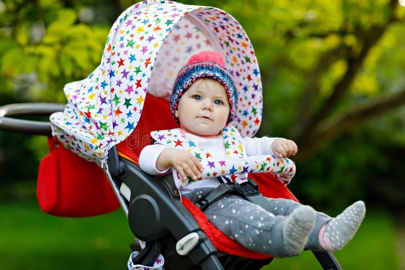 Bebê bonito pequeno bonito que senta-se na mamã do pram ou do carrinho de criança e da espera Criança de sorriso feliz com olhos  fotografia de stock royalty free