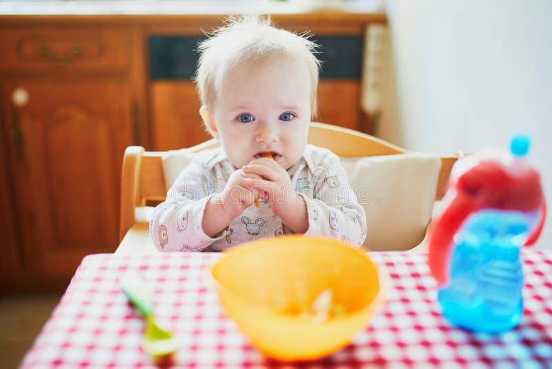 Bebê bonito que alimenta-se com alimento de dedo na cozinha foto de stock royalty free
