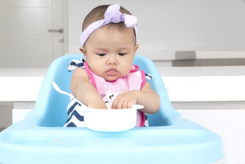 Bebê bonito que come o alimento na cozinha imagens de stock
