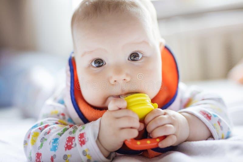 Bebê bonito que come o fruto no nibbler na cama em casa imagem de stock royalty free