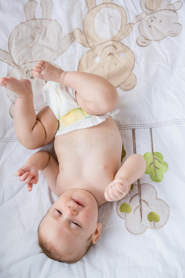 Bebê bonito que encontra-se na cama no quarto fotografia de stock