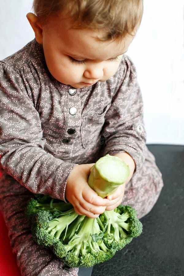 Bebê bonito que guarda brócolis em suas mãos, sentando-se no assoalho dentro foto de stock royalty free